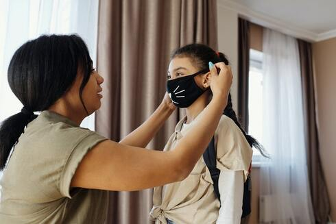 mom putting on daughter's face mask